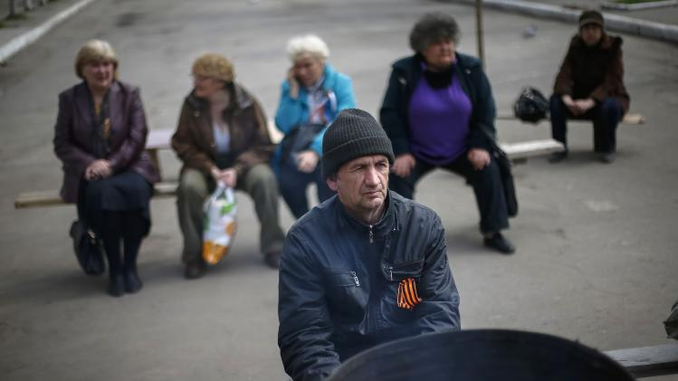 Pro-Russian protesters sit near barricades at the police headquarters in Slaviansk