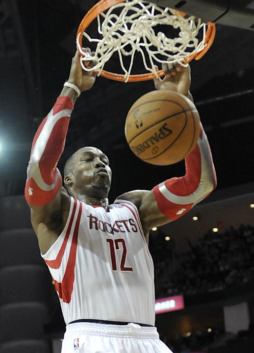 Houston Rockets' Dwight Howard hangs on the rim after dunking the ball against the Cleveland Cavaliers in the second half of an NBA basketball game Saturday, Feb. 1, 2014, in Houston. The Rockets
