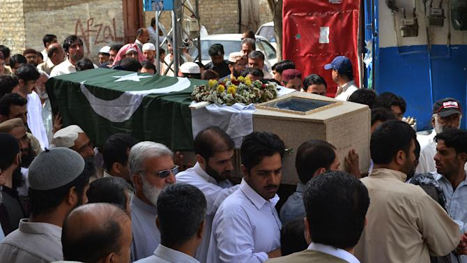 People carry the flag-wrapped casket of a high-ranking government official who was killed in Saturday's bombing at the Bolan Medical complex in Quetta, Pakistan, Sunday, June 16, 2013. The radical Lashkar-e-Jhangvi group claimed responsibility for the attacks on the hospital and a women's university bus. (AP Photo/Arshad Butt)