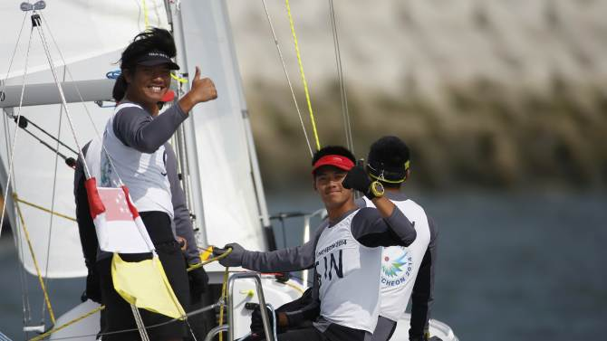 Team Singapore gives a thumbs-up as they celebrate defeating Malaysia during their men's semi-final match racing of the sailing competition during the 17th Asian Games in Incheon