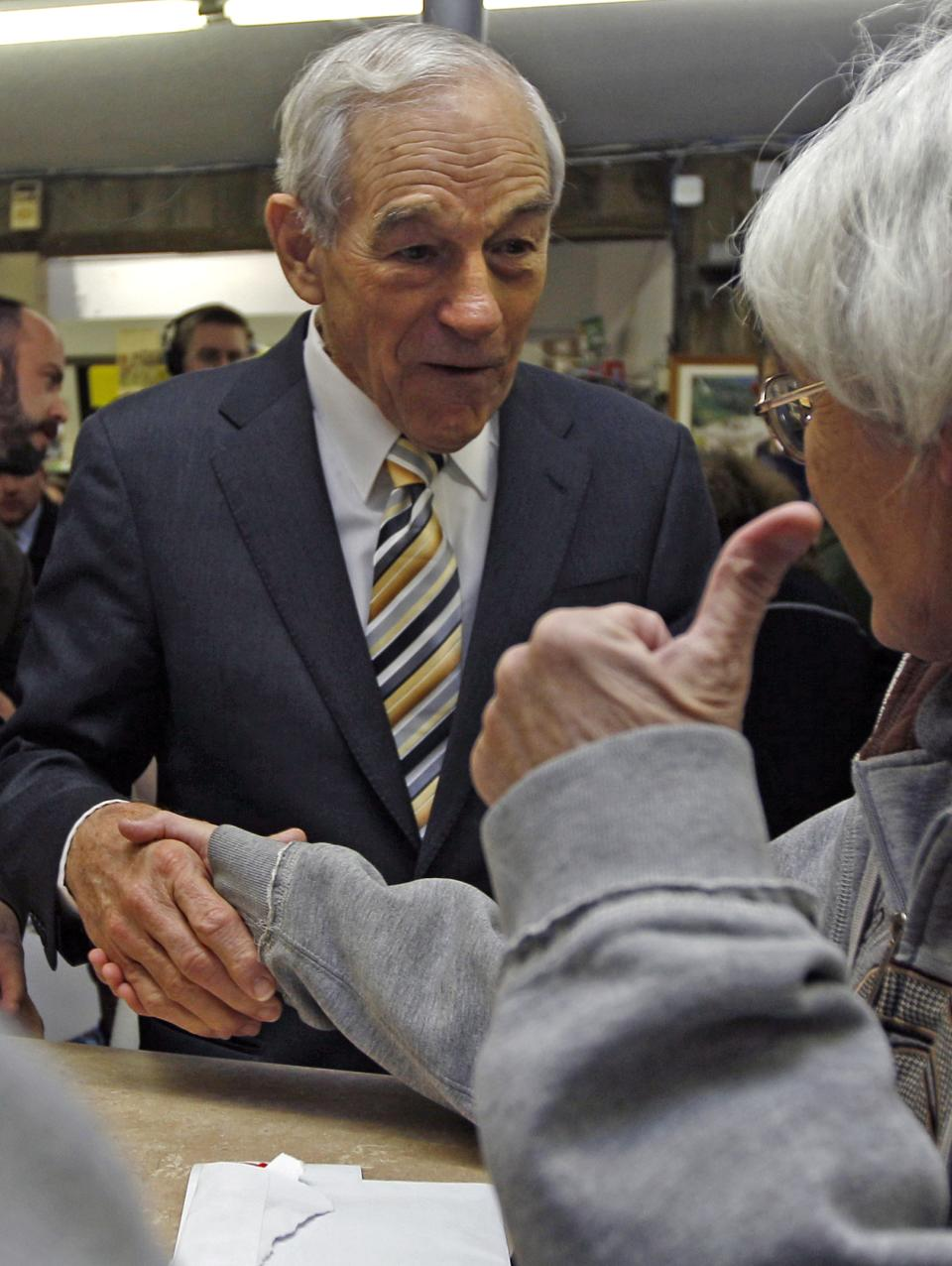 Republican presidential candidate Rep. Ron Paul, R-Texas, shakes hands while campaigning at Sandy's Variety Store in Manchester, N.H., Tuesday Dec. 20, 2011. (AP Photo/Charles Krupa)