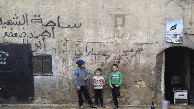 Boys stand by a wall in the old city of Aleppo