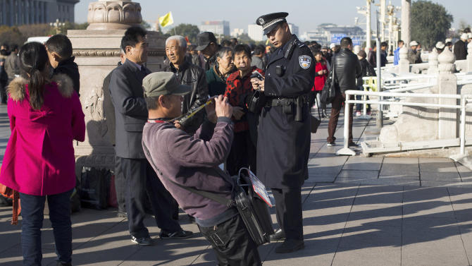 A vendor takes pictures for his customer in front of a policeman checking identities of people near Tiananmen Gate in Beijing Thursday, Nov. 1, 2012 as the all-important Party Congress approaches. Beijing usually tightens security for high-profile political events, and this one is the most pivotal for the Communist Party in 10 years. But sometimes the measures can pass into the downright bizarre.(AP Photo/Andy Wong)