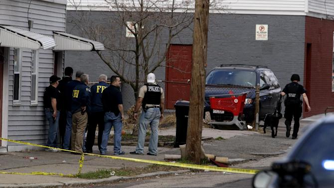 Law enforcement officials stand guard while searching for an individual believed to be involved in the Boston Marathon explosions in Watertown, Mass., Friday, April 19, 2013. The two suspects in the Boston Marathon bombing killed an MIT police officer and hurled explosives at police in a car chase and gun battle overnight that left one of them dead and his brother on the loose, authorities said Friday.  (AP Photo/Julio Cortez)