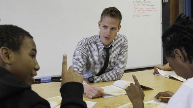 """In this Monday, May 7, 2012 photo, Chad Larsen Stauber, center, a student teacher at the Lafayette School in Chicago, works with students Devion Allen, left, and Jovante Ross, on their reading skills. The 26-year-old who just received his master's degree in education knows that later in 2012, he'll have to start paying off debt of about $100,000. """"This is going to be looming over my head the next 20 years,"""" Larsen-Stauber says. """"You've borrowed all of this money and it just comes due all of a sudden. When you're already going into a low-wage job and you know that a third of your salary is immediately going to be eaten up ... that's really frightening."""" It seems overwhelming, but he says, """"there never has been a regret in my mind. I knew when I started this program, I was 100 percent sure. ... If there was one job that I ever wanted, it was to be a teacher."""" (AP Photo/M. Spencer Green)"""