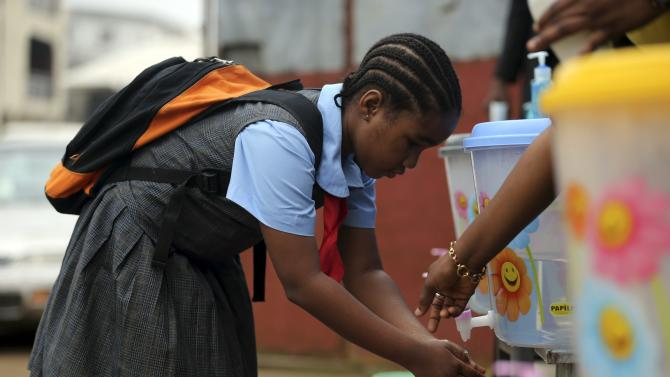 A pupil washes her hands with an improvised tap in front of the school premises, at the resumption of private schools, in Lagos
