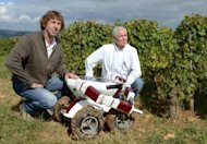 Christophe Millot (R) and Guy Julien pose in a vineyard with the Wall-Ye V.I.N. robot on September 13 near Chalon-sur-Saone in eastern France. The robot is one of a series being developed around the world aimed at vineyards struggling to find the labour they need