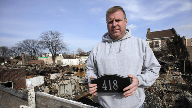 In this Sunday, Nov. 18, 2012 photo, Ray Marten poses with the street number sign recovered from the ashes of his fire-destroyed home in the Belle Harbor section of the Queens borough of New York. Marten is thankful that his teenage children are alive. The three of them narrowly escaped a fire that swept through their community the night Superstorm Sandy slammed into the East Coast. (AP Photo/Mark Lennihan)