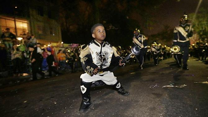 """Tudda Honore, 6, performs as a drum major with the """"Roots of Music"""" marching band during the Krewe of Bacchus Mardi Gras parade in New Orleans, Sunday, Feb. 10, 2013. (AP Photo/Gerald Herbert)"""
