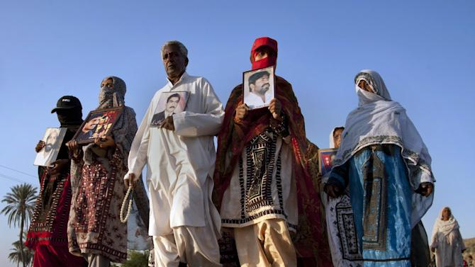 In this Tuesday, Nov. 19, 2013, photo, Pakistani families hold photographs of their relatives, who were allegedly abducted by Pakistani security forces, as they march toward Karachi, in Gadani, Pakistan. Baluch is one of roughly two dozen activists making the journey on foot from Quetta, the capital of southwest Baluchistan province, to the southern port city of Karachi to protest thousands of people who have gone missing over the years as Pakistani authorities have battled a separatist insurgency in Baluchistan. (AP Photo/Shakil Adil)