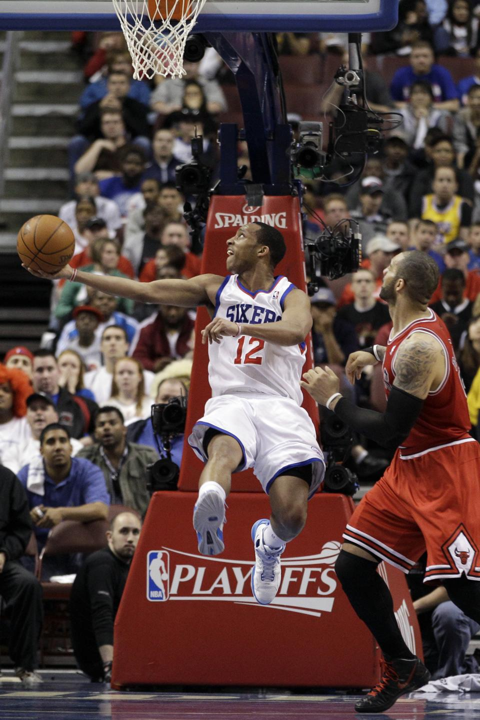 Philadelphia 76ers' Evan Turner (12)  goes up for a shot as Chicago Bulls' Carlos Boozer, right, defends in the first half of Game 6 in an NBA basketball first-round playoff series on Thursday, May 10, 2012, in Philadelphia. (AP Photo/Matt Slocum)