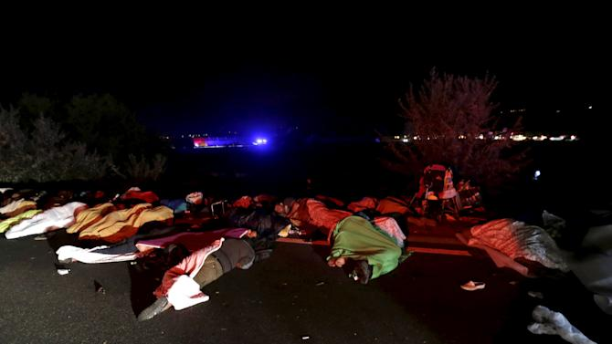 Migrants sleep as they wait for buses bound for Austria and Germany, along the M1 highway near Budapest, Hungary