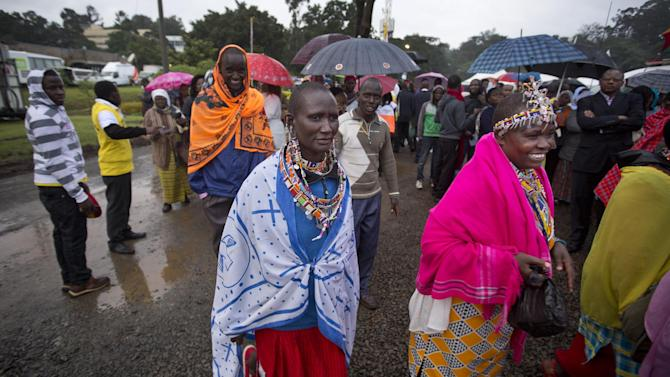 Maasai women arrive just after dawn in the rain and mud to attend a Mass to be given by Pope Francis at the campus of the University of Nairobi in Kenya Thursday, Nov. 26, 2015. Pope Francis is in Kenya on his first-ever trip to Africa, a six-day pilgrimage that will also take him to Uganda and the Central African Republic. (AP Photo/Ben Curtis)
