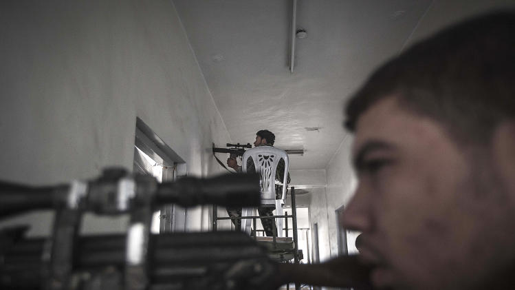 In this Tuesday, Oct. 30, 2012 photo, rebel fighters belonging to the Liwa Al-Fatah keep an eye on an enemy position from a school building during skirmishes with the Syrian army in the nearby Bustan Al-Pasha front line in Aleppo, Syria. (AP Photo/Narciso Contreras)
