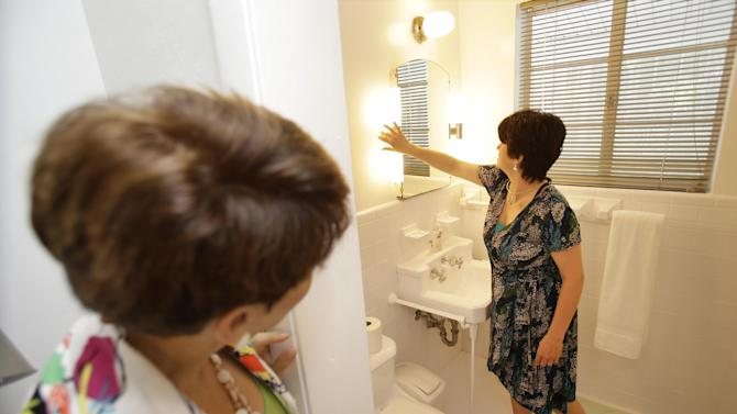In this Thursday, May 29, 2014 photo, prospective buyer Mary Tuttle, right, checks out antique lighting fixtures while looking at a home with real estate broker Nancy Dowson, left, with Keller Williams Realty, in Miami Shores, Fla. The National Association of Realtors reports, on Monday, Sept. 22, 2014, on sales of existing homes in August. (AP Photo/Wilfredo Lee)