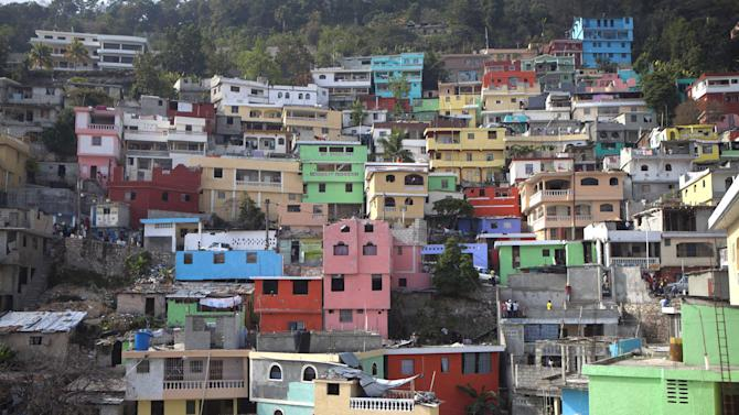 """In this picture taken March 21, 2013, homes painted in bright colors cover a hill in Jalousie, a cinder block shantytown in Petionville, Haiti. Workers this month began painting the concrete facades of buildings in Jalousie slum a rainbow of colors, inspired by the dazzling """"cities-in-the-skies"""" of well-known Haitian painter Prefete Duffaut, who died last year. (AP Photo/Dieu Nalio Chery)"""