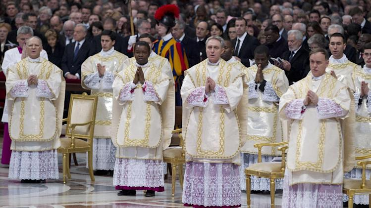From left, newly elected bishops Angelo Vincenzo Tani, of Italy, Fortunatus Nwachukwu, of Nigeria, Georg Ganswein, of Germany, and Nicolas Marie Denis Thevenin pray as they attend an Epiphany mass celebrated by Pope Benedict XVI in St.Peter's Basilica at the Vatican, Sunday, Jan. 6, 2013. The Epiphany day, is a joyous day for Catholics in which they recall the journey of the Three Kings or Magi to pay homage to Baby Jesus. (AP Photo/Andrew Medichini)