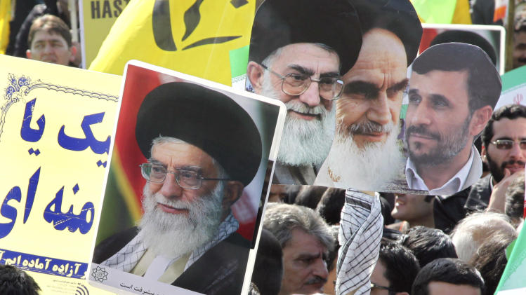Iranians flash the victory sign as they hold posters showing President Mahmoud Ahmadinejad, right, late Ayatollah Khomeini, second right, and Supreme Leader Ayatollah Ali Khamenei, center and left, at a rally commemorating the anniversary of 1979 Islamic revolution that toppled the country's pro-Western monarchy and brought Islamic clerics to power, in Azadi Square, Tehran, Iran, Sunday, Feb. 10, 2013. In his statements to the rally, Ahmadinejad said he is ready to have direct talks with United States if the West stops pressuring his country. (AP Photo/Vahid Salemi)
