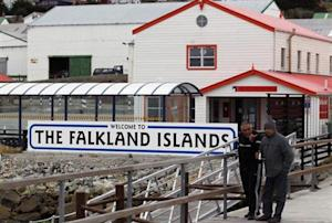 "Argentine Falklands War veterans walk next to a ""Welcome to the Falkland Islands"" sign in Port Stanley"