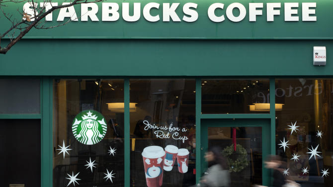 """Pedestrians walk past a branch of the Starbucks cafe chain in west  London, Monday, Dec.  3, 2012.  A committee of British lawmakers says the government should """"get a grip"""" and clamp down on multinational corporations that exploit tax laws to move profits generated in Britain to offshore domains.The committee says major multinationals including Starbucks, Google and Amazon are guilty of immoral tax avoidance. Starbucks announced it is reviewing its British tax practices in a bid to restore public trust. (AP Photo/Alastair Grant)"""