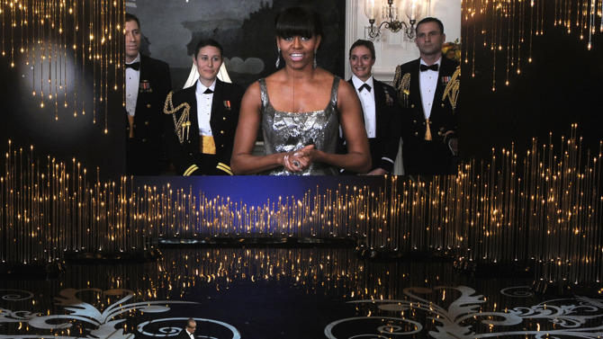 FILE - In this Feb. 24, 2013 file photo, first lady Michelle Obama, appearing via video link, and actor Jack Nicholson present the award for best picture during the Oscars ceremony at the Dolby Theatre in Los Angeles. As seen in this photo, the first lady wore a sleeveless, scoop neck gown for the occasion. But Iran's semi-official Fars news agency ran an altered photo that covered her shoulders and neckline with added material to make her gown look less revealing. (Photo by Chris Pizzello/Invision/AP, File)
