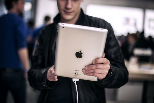 <p>Photo illustration shows a customer holding an Apple iPad. The US technology giant has paid $60 million to a Chinese firm to settle a long-running dispute over the iPad trademark in China, a court said Monday.</p>