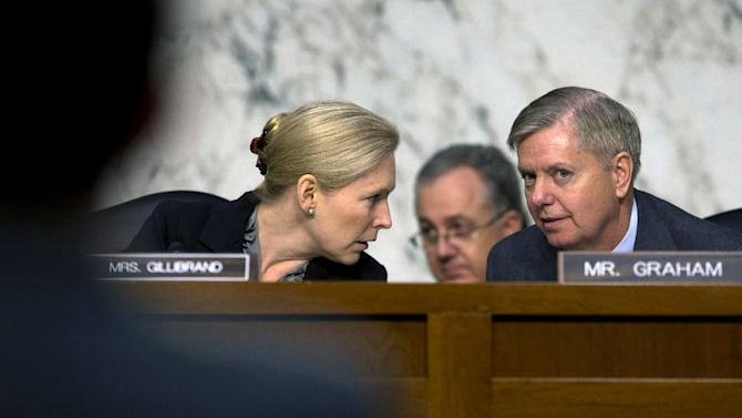 Senate subcommittee on Personnel Chair, Sen. Kirsten Gillibrand, D-N.Y., left, talks with the subcommittee's ranking Republican, Sen. Lindsey Graham, R-S.C., on Capitol Hill in Washington, Wednesday, March 13, 2013, during the subcommittee's hearing on sexual assault in the military. (AP Photo/Carolyn Kaster)