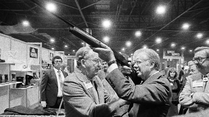 "FILE - In this Nov. 14, 1984 file photo, former President Jimmy Carter sights down the barrel of a shotgun as Reinhart Fajen, a gunstock manufacturer, checks the fit, in Atlanta as Carter stopped during a visit to the national shooting sports foundation shot show at the World Congress Center. The White House has released a photo of President Barack Obama firing a gun, two days before he is set to travel to Minnesota to discuss gun control. It shows Obama shooting at clay targets on the range at Camp David, the presidential retreat in Maryland, where he says he engages in the sport ""all the time."" The image was released at a time when Obama is pushing a package of gun-control measures in response to the Newtown, Conn., school shooting. But the image of a U.S. president holding a gun is certainly nothing new. (AP Photo/Ric Feld, File)"