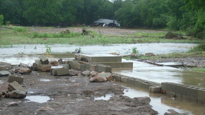 This June 1, 2013 photo provided by the National Oceanic and Atmospheric Administration shows the foundation of a house, foreground, that Brushy Creek washed away in Montgomery County between Oden and Mount Ida, Ark. Flash flooding and tornadoes killed three people in Arkansas late Thursday and Friday. Three others were missing in floods that followed 6 inches of rain in the rugged Ouachita Mountains near Y City, 125 miles west of Little Rock. The house appears in the background. (AP Photo/NOAA)