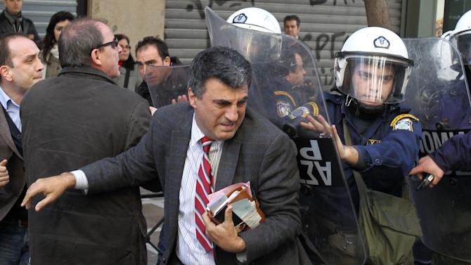 Riot police use shields to move away supporters of detained protesters from outside the Labor Ministry in Athens, Wednesday, Jan. 30, 2013. Protesters from a Communist-backed labor union forced their way into a government building and clashed with police who used tear gas to expel them. Members of the union are protesting planned reforms to the country's pension and income contribution system — part of ongoing austerity cuts demanded by Greece's euro partners and the International Monetary Fund who are keeping the country afloat with emergency loans. (AP Photo/Thanassis Stavrakis)