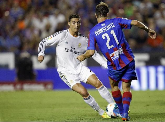 Real Madrid's Cristiano Ronaldo from Portugal duels for the ball with Levante's Andreas Ivanschitz from Austria during their La Liga soccer match at the Ciutat de Valecia stadium in Valencia, Spain, S