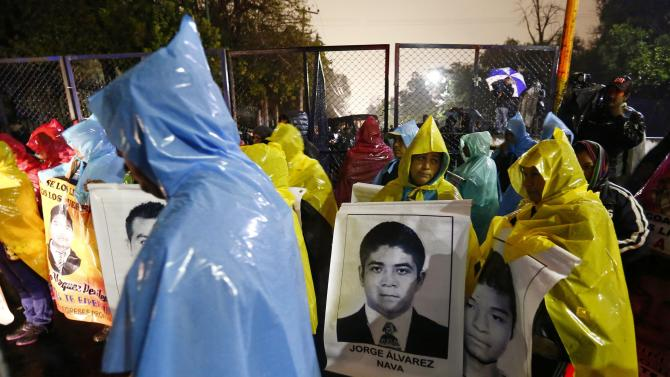 Relatives hold photos of some of the 43 missing trainee teachers of the Ayotzinapa teachers' training college during a protest in Mexico City