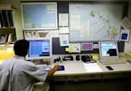 A geophysicist at the National Weather Service Pacific Tsunami Warning Center, monitors computer tracking systems in 2004. The US National Weather Service computer network was hacked this week, with a group from Kosovo claiming credit and posting sensitive data, security experts said Friday