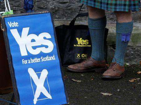 A supporter of the 'Yes' campaign stands outside a polling station during the referendum on Scottish independence in Pitlochry