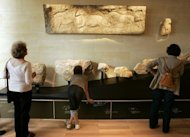 Visitors observe the first artifacts from the carved caves in Dordogne, France at a museum in 2004. A massive block of limestone from these caves contains what scientists believe are the earliest known engravings of wall art dating back some 37,000 years