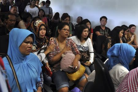 Family members of passengers on board AirAsia flight QZ8501wait for information inside a crisis centre at Juanda Airport in Surabaya, East Java