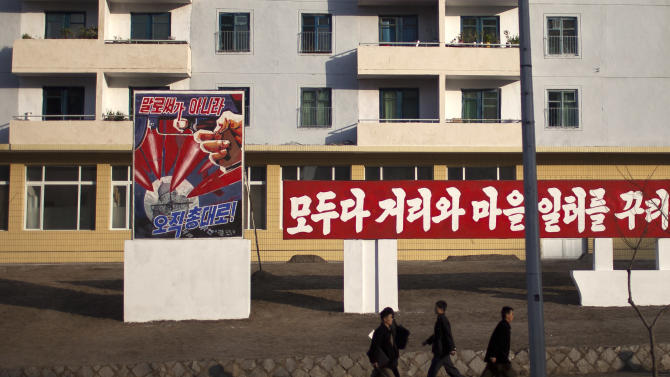 """ADDS THE TRANSLATION OF THE POSTER - Morning commuters walk past a poster showing weapons targeting the White House building on a street in Pyongyang, North Korea, Friday, April 19, 2013. The poster reads: """"Not by words, but only through arms"""" (AP Photo/Alexander F. Yuan)"""