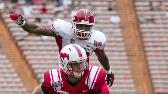 Fresno State safety Phillip Thomas, bottom, and linebacker Tristan Okpalaugo, top, watch as SMU quarterback Garrett Gilbert (11) breaks a tackle and runs in for a touchdown in the second quarter of the Hawaii Bowl NCAA college football game Monday, Dec. 24, 2012, in Honolulu. (AP Photo/Eugene Tanner)