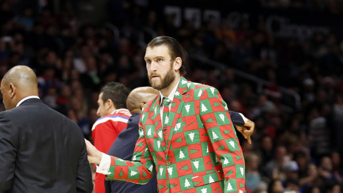 Los Angeles Clippers' Spencer Hawes wears a Christmas themed suit as he attends the NBA basketball game against the Golden State Warriors during the first half of an NBA basketball game Thursday, Dec. 25, 2014, in Los Angeles. (AP Photo/Danny Moloshok)