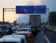 A traffic jam is seen as a wildfire destroys the forest in Ller near La Junquera (Girona), close to the Spanish-French border. The wildfire whipped up by strong winds left three people dead Sunday and about 100 people injured and forced thousands of residents to remain indoors, officials said