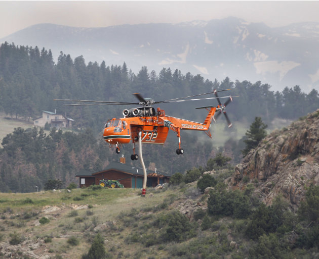 A Erickson Air Crane firefighting helicopter flys to a pond to refill its tank while fighting the High Park wildfire, west of Fort Collins, Colo., on Friday, June 15, 2012. The wildfire started Saturday and has burned over 50,000 acres.
