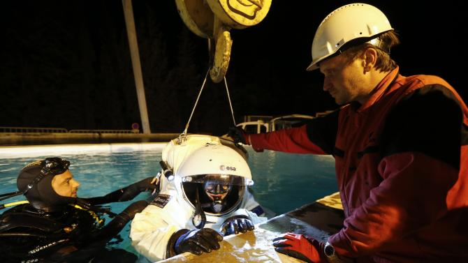 Comex Space division manager Weiss checks the Gandolfi space suit of National Diving School director Vincent with Comex's astronaut-diver Bonini during training procedures in a swimming pool in Marseille