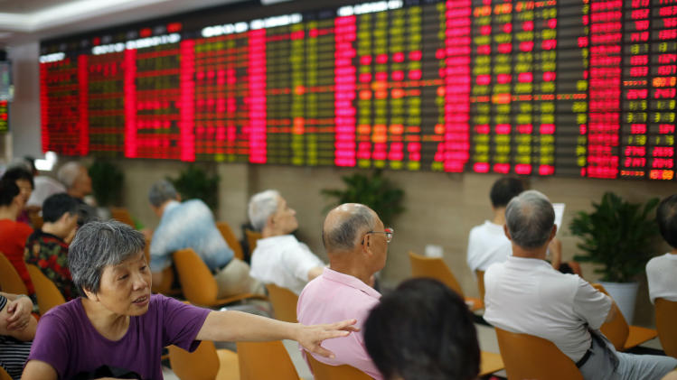 Investors look at the stock price monitor at a private securities company in Shanghai, China, Wednesday, Aug. 21, 2013. Asian stock markets were choppy Wednesday as traders waited for hints from the U.S central bank about when it will begin to reduce its massive stimulus effort. (AP Photo)