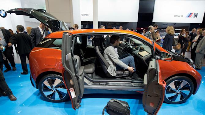 Journalists view the i3 electric car by car manufacturer BMW at the Frankfurt Motor Show (IAA) in Frankfurt Main, Germany, Monday, Sept. 9, 2013. The 65th IAA runs Sept 12 through 22, 2013. (AP Photo/dpa, Boris Roessler)