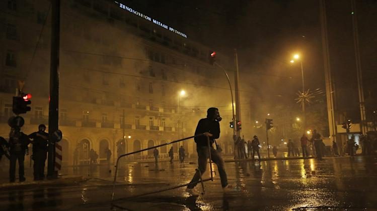 A protester carries a barrier during clashes with police in front of the parliament in Athens, Wednesday Nov. 7, 2012. Greece's fragile coalition government faces its toughest test so far when lawmakers vote later Wednesday on new painful austerity measures demanded to keep the country afloat, on the second day of a nationwide general strike. The 13.5 billion euro ($17.3 billion) package is expected to scrape through Parliament, following a hasty one-day debate. (AP Photo/Lefteris Pitarakis)