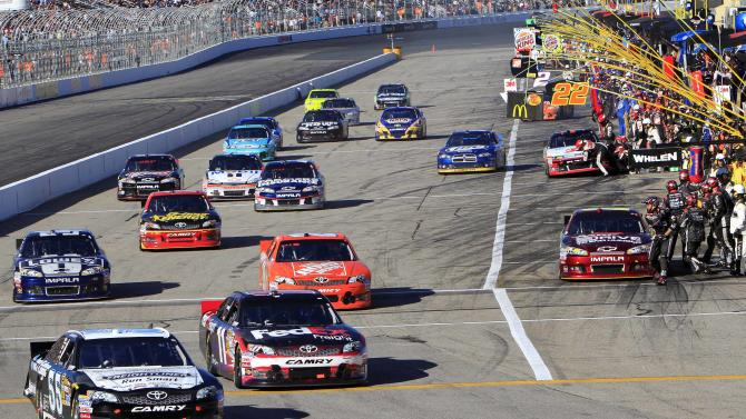 Brian Vickers edges Denny Hamlin out of the pits during the NASCAR Sprint Cup Series auto race at New Hampshire Motor Speedway, Sunday, Sept. 23, 2012, in Loudon, N.H. (AP Photo/ Jim Cole)