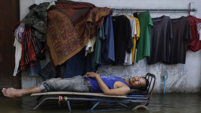 A Thai worker sleeps on top of a hand cart to keep him dry from floodwaters near the swollen Chao Phraya River in Bangkok, Thailand, Saturday, Oct. 29, 2011. The complex network of flood defenses erected to shield Thailand's capital from the country's worst floods in nearly 60 years was put to the test Saturday as coastal high tides hit their peak. (AP Photo/Aaron Favila)
