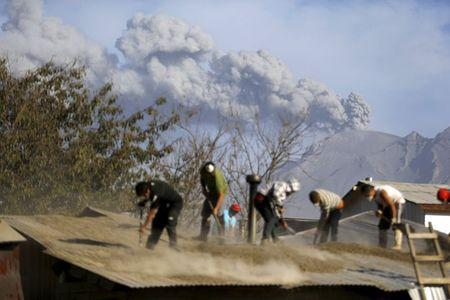 People clean an ash-covered roof of a house in Ensenada town