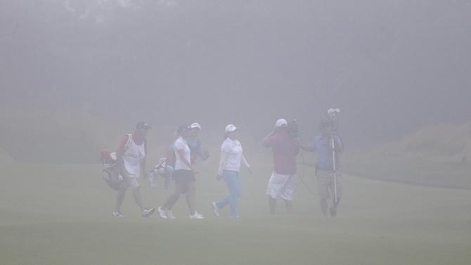 A television cameraman works in front of Inbee Park, center, from South Korea, in dense fog on the 18th hole during the second round at the U.S. Women's Open golf tournament at Sebonack Golf Club in Southampton, N.Y., Friday, June 28, 2013. Play was eventually suspended due to the fog. (AP Photo/Seth Wenig)