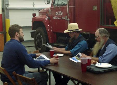 Eudaly, an executve with Flatiron Energy Partners, talks with members of the Ohio Amish community at the Deersville, Ohio, Volunteer Fire Department